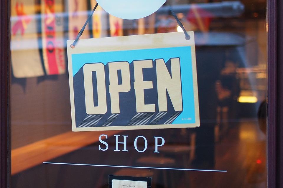 porta de loja com placa de aberto